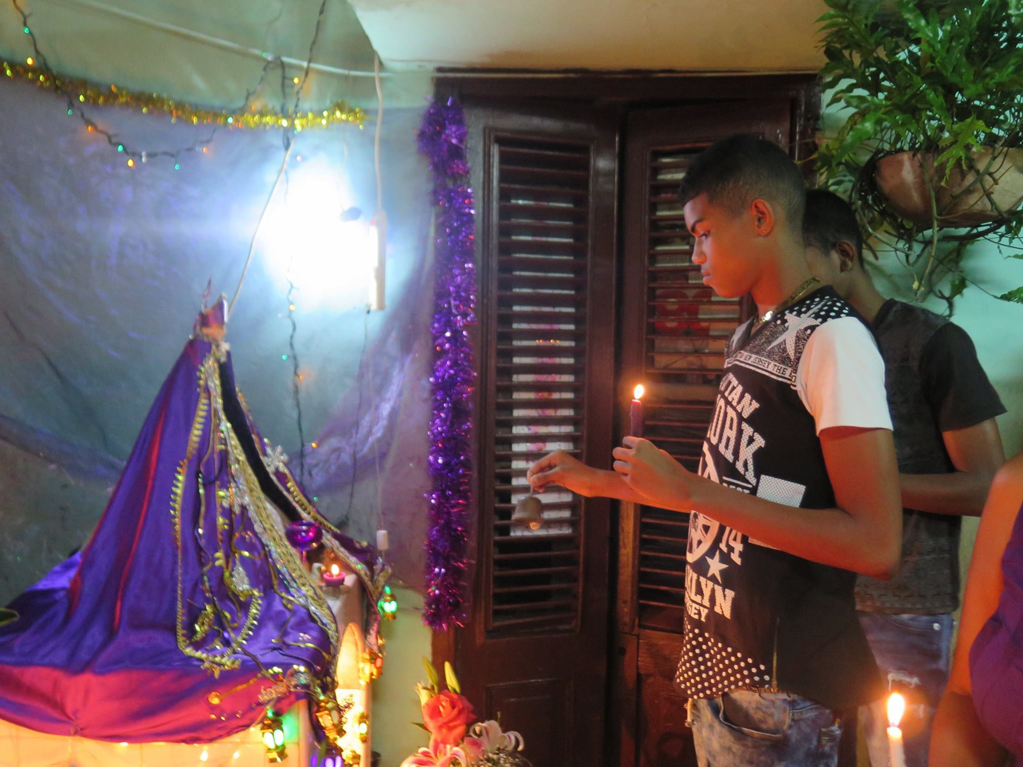 san lazaro, saint lazaro, celebration, worship, religion, santeria, catholicism, catholic, cuba, cuban, cuban streets, cuban celebration, streets of cuba, saint, patron saint of suffering, caribbean island, worshippers, boy, streets of cuba, cuban street altar, altar, candles