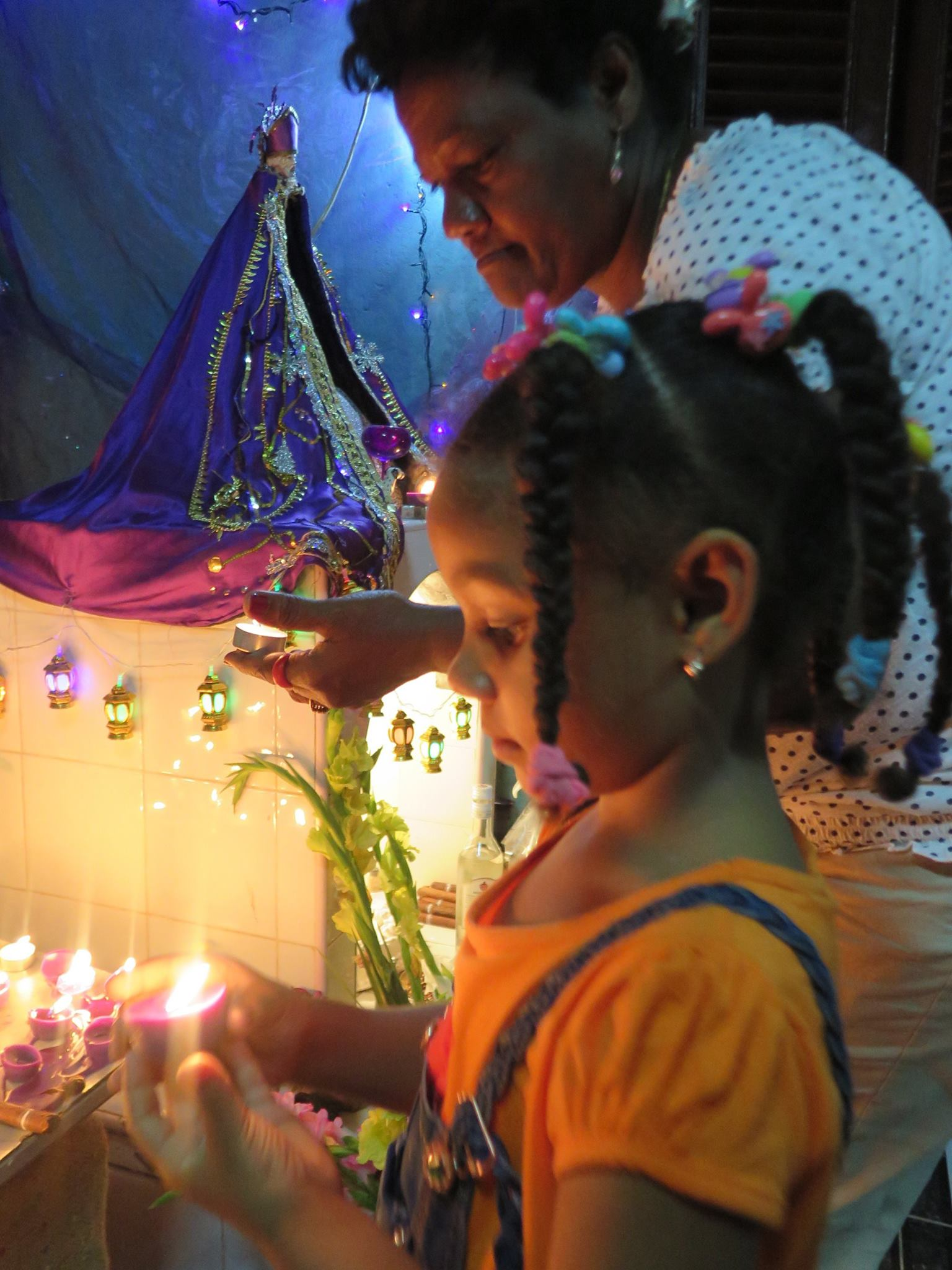 san lazaro, saint lazaro, celebration, worship, religion, santeria, catholicism, catholic, cuba, cuban, cuban streets, cuban celebration, streets of cuba, saint, patron saint of suffering, caribbean island, worshippers, girl, candle, light, lights, family